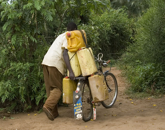 Man on bike with 5 jerry cans of water. 10-01-07
