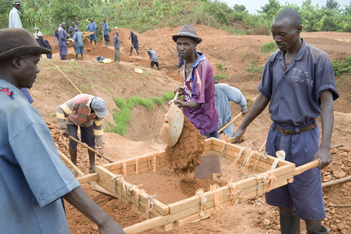 TIG members sifting dirt for making bricks