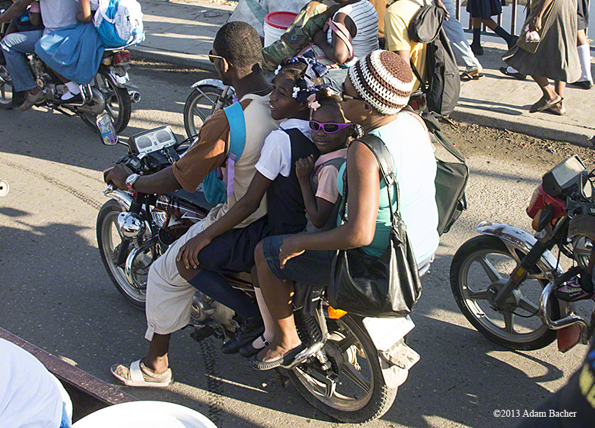 School girl in sunglasses on motorcycle, Cap Haitian, Haiti